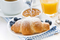 Fresh croissant with orange jam, blueberries and coffee. For traditional breakfast, closeup, horizontal Stock Photography