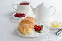 Fresh croissant with raspberry and tea for breakfast. On white wooden table Royalty Free Stock Image