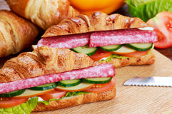 Fresh croissant with salami, cheese and vegetables Stock Photo
