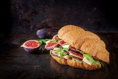 Fresh croissant sandwich with brie cheese arugula and figs. Delicious breakfast. Tasty food stock image