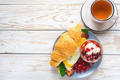 Fresh croissant sandwich, homemade yogurt, pomegranate and tea. Fresh croissant  with orange yolk fried egg, bacon, spinach and cheese, homemade yogurt with Royalty Free Stock Photography