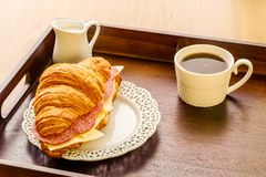 Fresh croissant sandwich with sausages and cheese with coffee breakfast on a tray. Royalty Free Stock Photography