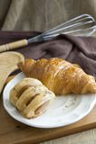 Fresh croissant and sausage roll Stock Images