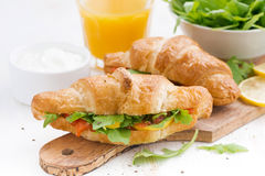 Fresh croissant stuffed with fish and arugula for breakfast Royalty Free Stock Photography