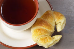 Fresh croissant and tea. Fresh croissant and a cup of tea on the saucer on the table Royalty Free Stock Photography