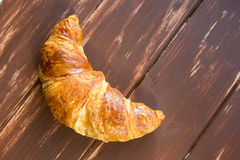 Fresh croissant at wooden table Royalty Free Stock Photo