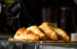 Fresh croissants. Four croissants in a bar with a dark blurred background royalty free stock image