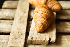 Fresh croissants on aged wood box and plank, close up, golden crust, flaky pastry, rustic vintage style Royalty Free Stock Images