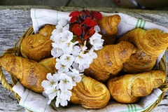 Fresh croissants in a basket from bakery with flowers. Fresh french croissants in a basket from bakery on wooden background Royalty Free Stock Image