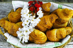Fresh croissants in a basket from bakery with flowers. Fresh french croissants in a basket from bakery on wooden background Royalty Free Stock Photography