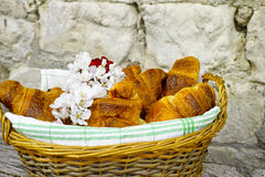 Fresh croissants in a basket from bakery. Fresh french croissants in a basket from bakery on background with old stone wall Stock Image