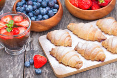 Fresh croissants and berries  with cup of fruit tea on old wooden Royalty Free Stock Photography