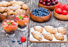 Fresh croissants and berries with cup of fruit tea on old wooden Royalty Free Stock Photos