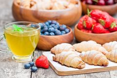 Fresh croissants and berries with cup of green tea on old wooden Stock Image