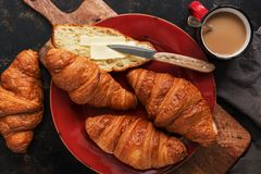 Fresh croissants with butter and coffee with milk on a dark background. Top view, flat lay royalty free stock image