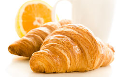 Fresh croissants, coffee and orange over white back Royalty Free Stock Image