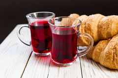 Fresh Croissants and cups of hot hibiscus tea Stock Images