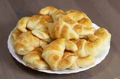 Fresh croissants. Dozen of croissants over white plate on the table Royalty Free Stock Photos
