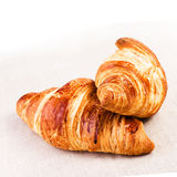 Fresh Croissants on linen tablecloth on a table, closeup. Stock Photo