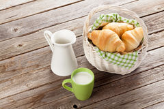 Fresh croissants and milk. Fresh croissants basket and milk on wooden table Stock Photos