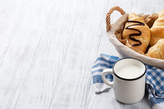 Fresh croissants and milk. Fresh croissants basket and milk on wooden table. View with copy space Royalty Free Stock Images