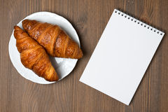 Fresh croissants on a plate and notepad, top view Stock Image