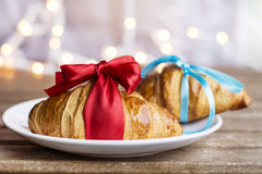 Fresh croissants  with red ribbon  and blue ribbon on a bokeh background. Fresh croissants on a wooden table.Christmas style Stock Photography