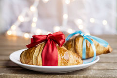 Fresh croissants  with red ribbon  and blue ribbon on a bokeh background. Fresh croissants on a wooden table.Christmas style Royalty Free Stock Photos
