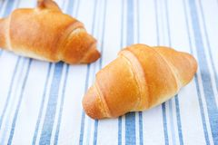 Fresh croissants on a striped linen towel. Freshly baked bakery products close-up. The concept of organic, farm food. The view stock photography