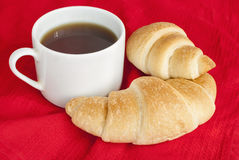 Fresh croissants with tea for breakfast. Fresh croissants with tea on a red fabric. Selective focus Stock Photography