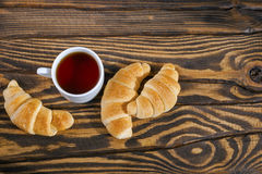 Fresh croissants with tea for breakfast. Top view. Selective focus Royalty Free Stock Images