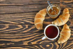 Fresh croissants with tea and jam for breakfast. Top view. Selective focus Royalty Free Stock Photo