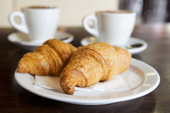 Fresh croissants. Two fresh croissants and coffee cups on a background in caf Royalty Free Stock Image