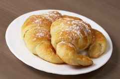 Fresh croissants. Two croissants over white plate on the table Royalty Free Stock Images