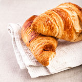 Fresh Croissants on a white linen napkin on beige tablecloth  ba Stock Image