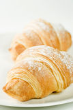 Fresh croissants on white plate with powdered sugar Royalty Free Stock Photos