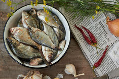 Fresh crucian. On a wooden table and spices Royalty Free Stock Photo