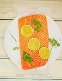 Fresh, crude fillet of a salmon with slices of a lime and greens Stock Images