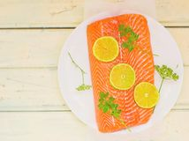 Fresh, crude fillet of a salmon with slices of a lime and greens Stock Photo