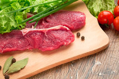 Fresh, crude, raw stakes from meat veal on a wooden chopping board with setion. Fresh, crude stakes from meat veal on a wooden chopping board with setion,black Stock Photo