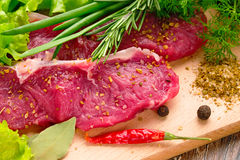 Fresh, crude, raw stakes from meat veal on a wooden chopping board with setion Royalty Free Stock Images