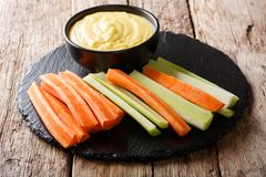Fresh crunchy carrots and celery with cheese dip on a close-up. Fresh crunchy carrots and celery with cheese dip on a close-up on the table. horizontal Stock Photography