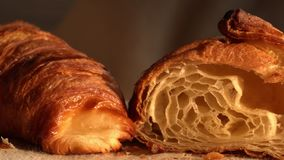 Fresh crusty croissants with puff texture. Close-up shot of appetizing crusty croissants. One is cut in a half to see its layered and puff dough texture stock video