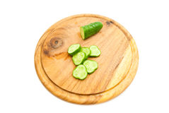 Fresh cucumber on cutting board. Half a fresh cucumber with slices on cutting board Royalty Free Stock Images