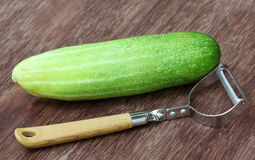 Fresh cucumber with peeler Royalty Free Stock Photography