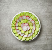 Fresh cucumber and radish slices. Plate of fresh cucumber and radish slices on gray kitchen table, top view Royalty Free Stock Images