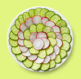 Fresh cucumber and radish slices. Plate of fresh cucumber and radish slices on green background, top view Royalty Free Stock Images
