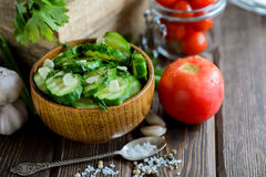 Fresh cucumber salad with fennel and garlic in bowl. On wooden board Stock Photo