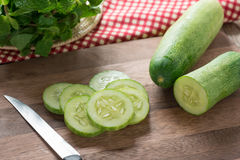 Fresh cucumber slices on wood cutting board. Stock Photos