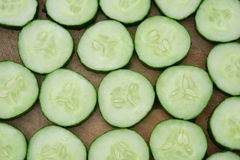 Fresh cucumber slices on wooden chop board Royalty Free Stock Images